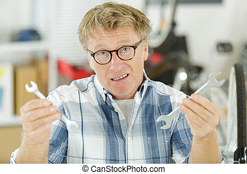 confused man showing at a pipe wrench