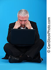 Confused middle-aged businessman with laptop