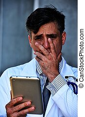 Confused Minority Male Doctor With Tablet