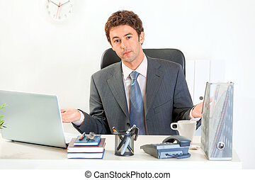 Confused modern business man sitting at office desk