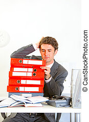 Confused modern businessman sitting at office desk with pile of folders