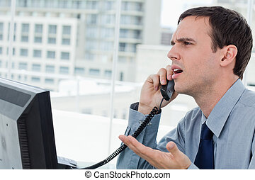 Confused office worker on the phone in his office