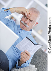 confused old man reading manual at home