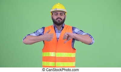 Confused overweight bearded Indian man construction worker ...