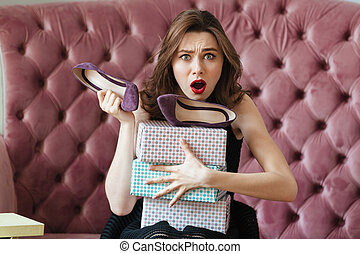 Confused screaming young lady sitting on sofa