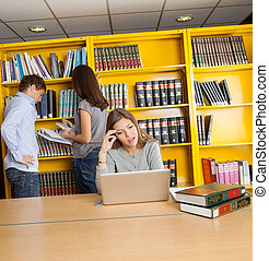 Confused Student Looking At Laptop In University Library