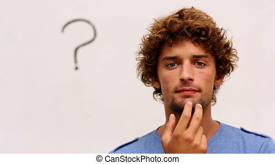 Confused student standing in front of question mark - ...