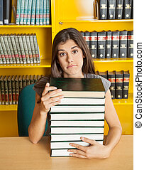 Confused Student With Stacked Books Sitting At Table In Library