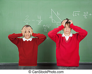 Confused Teenage Students Standing Against Board - Portrait...