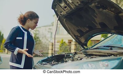 Confused woman looking at broken car engine on street - ...