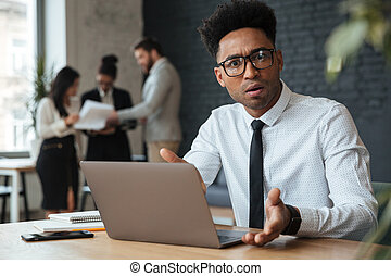 Confused young african businessman