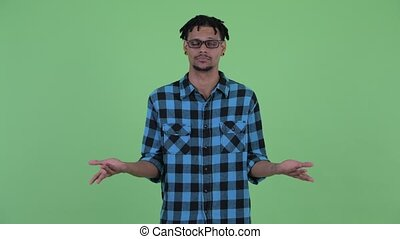 Confused young African hipster man shrugging shoulders