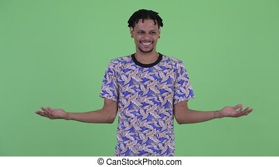 Confused young African man shrugging shoulders