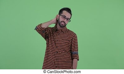Confused young bearded Persian hipster man scratching head -...