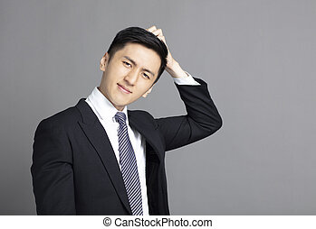 confused young businessman scratching his head