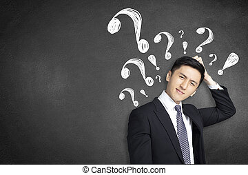 confused young businessman scratching his head with question mark