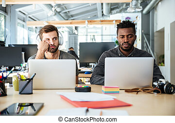 Confused young colleagues sitting in office coworking