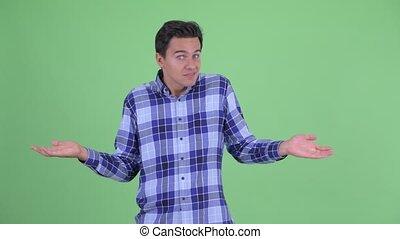 Confused young handsome hipster man shrugging shoulders