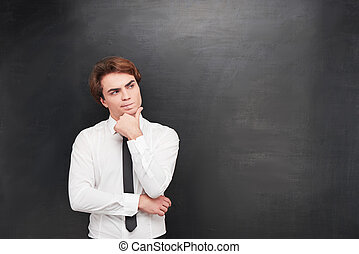 Confused young man on chalkboard background