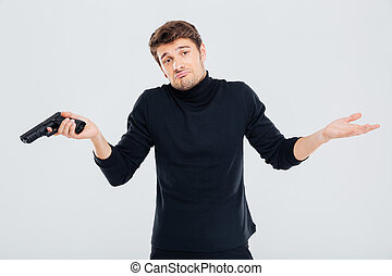 Confused young man with gun shrugging his shoulders