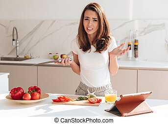 Confused young woman holding knife and shrugging shoulders