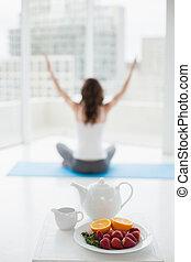 confuso, toned, mujer joven, sentado, en, meditación, postura, con, alimento sano, en, primer plano, en, condición física, estudio