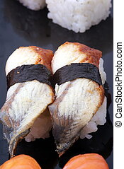 Conger eel nigiri sushi on the black plate.