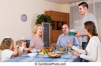 Young man congratulating heartily family member at home.