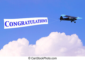 An airplane towing a banner with the word Congratulations in blue, good for male related themes or birth of a baby boy