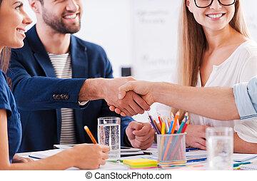 congratulations!, close-up, de, pessoas negócio, em, esperto casual, desgaste, apertar mão, e, sorrindo, enquanto, sentar tabela, junto