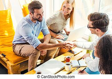 congratulations!, dois, alegre, homens jovens, sentando, em, a, escrivaninha madeira, em, escritório, e, apertar mão, enquanto, dois, mulheres bonitas, olhar, lhes, e, sorrindo