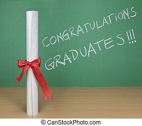 Congratulations graduates written on a chalkboard with a diploma on forefround.