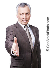 Congratulations! Portrait of cheerful mature man in formalwear stretching out hand for shaking while standing against white background