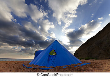 Conical tent on summer beach in evening