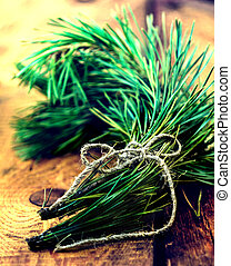 Conifer branch tied with ribbon on wooden old rustic background