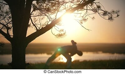 Coniferous tree in front of silhouette man performs capoeira on the hill at sunset