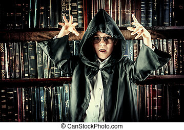 conjure - A boy in black cape with hood stands in the...
