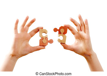 Human hands connecting two puzzle pieces together, over white background