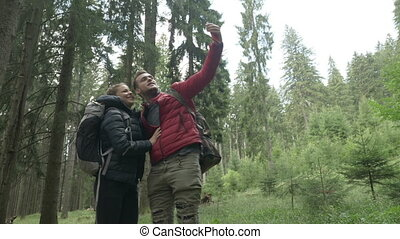 Connected by technology young couple of hikers using smartphone for video call in forest sharing the trip experience with friends