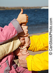 Connected hands of adults and child as symbol of unity of family. Thumb is lifted upwards!