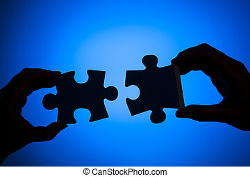 Silhouette of two hands connecting pieces of a puzzle on a blue background