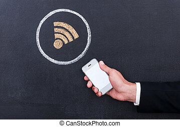Connecting the internet. Concept of human hand holding telephone against sharing symbol chalk drawing on blackboard