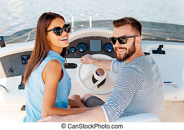 Conquering new marine ways together. Cheerful young couple looking at camera and smiling while driving yacht