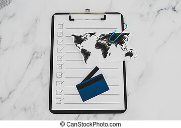 conquering the global markets, world map and to do list with text next to payment card and price tags on clipboard