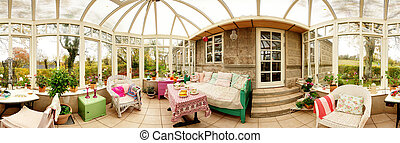 conservatory interior with sofa and chairs. panoramic image of glass extension