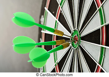 Consistency - Three green darts pinned on the center of ...