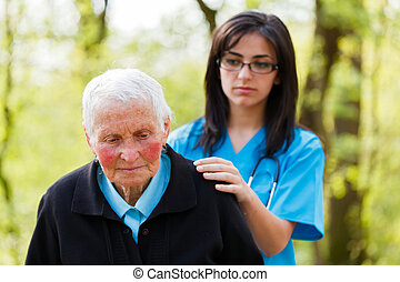 Consoling - Kind nurse in blue consoling sad senior patient.