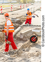 Construcion workers laying brick pavement on a sunny day