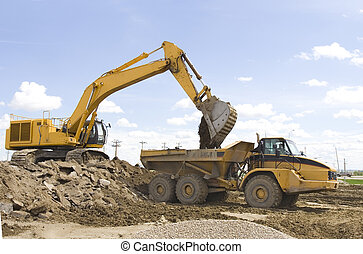A hoe filling up a dump truck