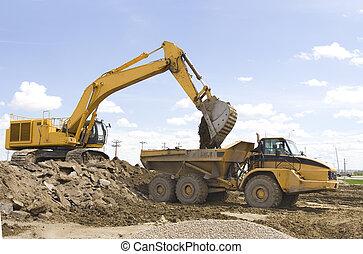 construction - A hoe filling up a dump truck